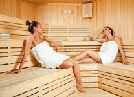 Beautiful young females relaxing in wooden spa room, eyes closed