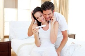 Enamoured couple finding out results of a pregnancy test sitting on the bed
