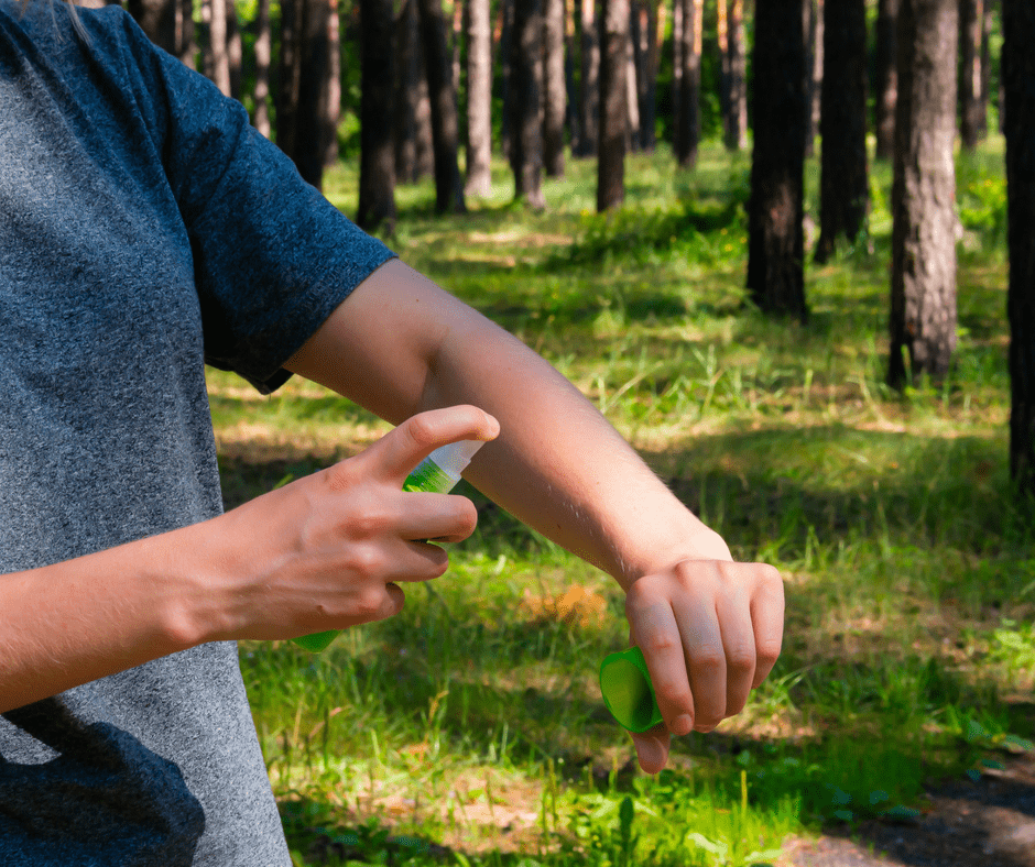 man spraying homemade bug spray on his arm in the woods