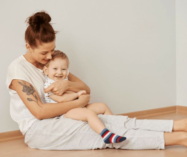 Mom sitting on the floor against the wall holding small son on her lap