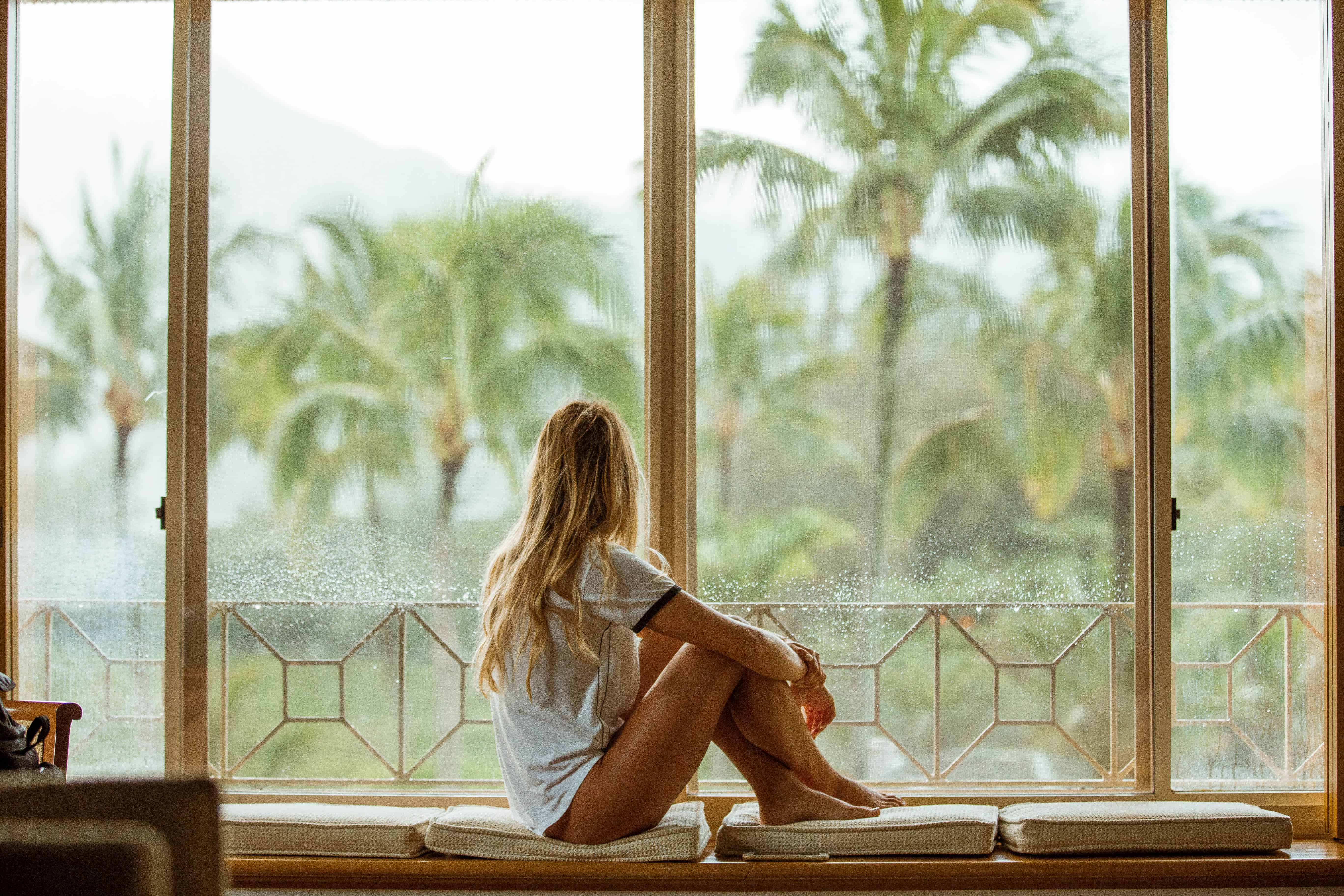 woman looking out windows with palm trees in the distance