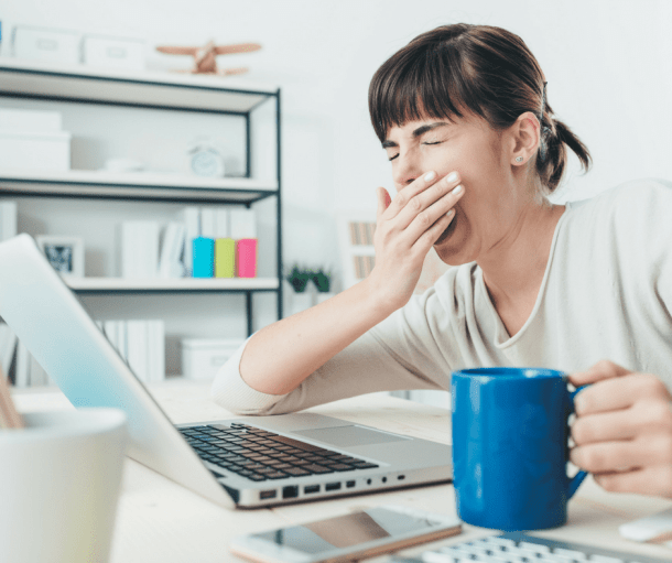 woman yawning in front of a laptop