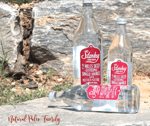 three Starkey spring water bottles on a rock in front of large rocks