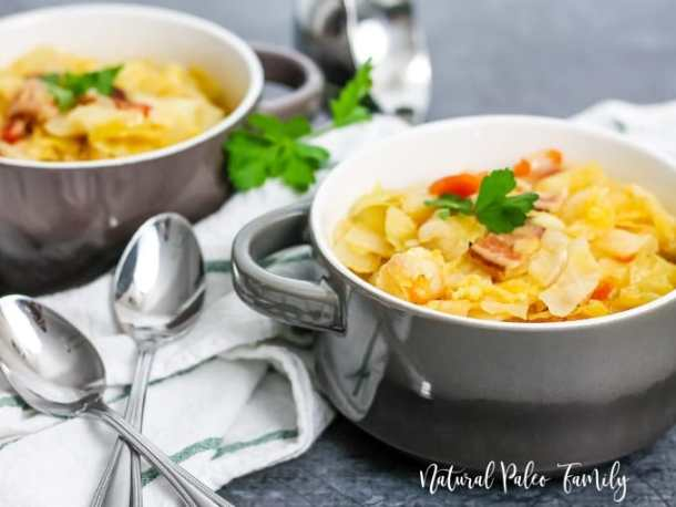 two bowls of cabbage bacon soup on white napkin