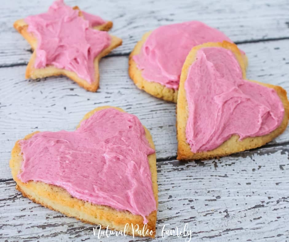 four pink frosted heart shaped cookies on white wood