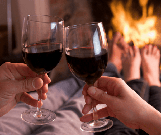 man and woman clinking wine glasses in front of a fire