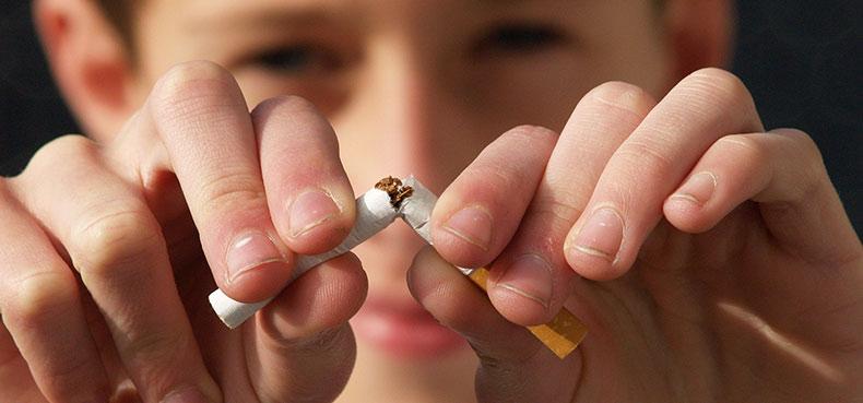 Personne qui casse une cigarette pour arrêter de fumer