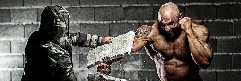 Homme musclé qui boxe une plaque en béton et l'explose