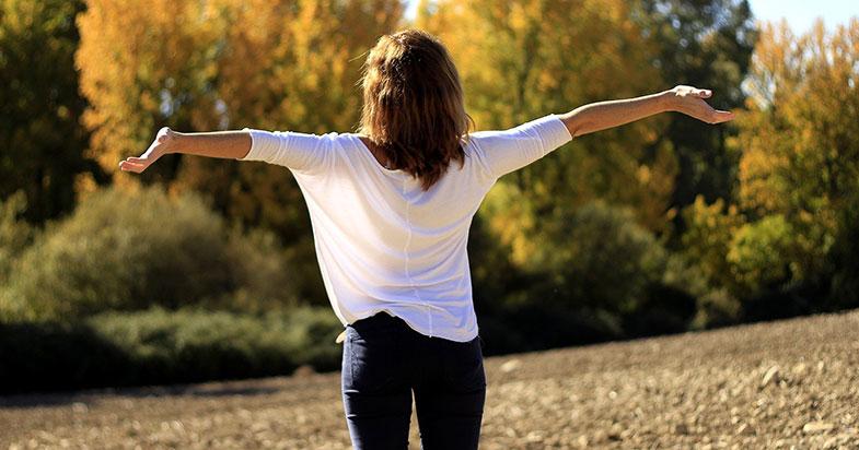 Joie et santé : femme qui lève les bras vers le soleil