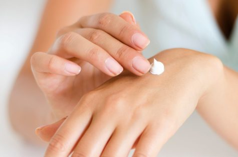 woman putting cream on hand