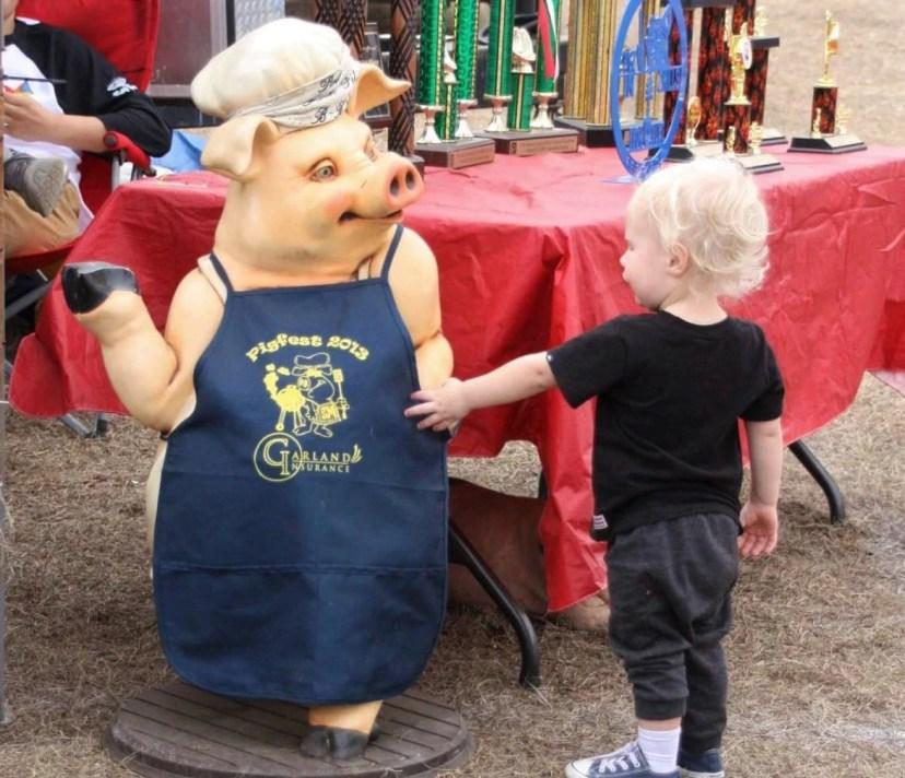 child shakes pig paw