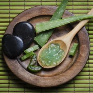 Aloe vera gel on wood spoon, with aloe leaves, black rocks, all on bamboo matt