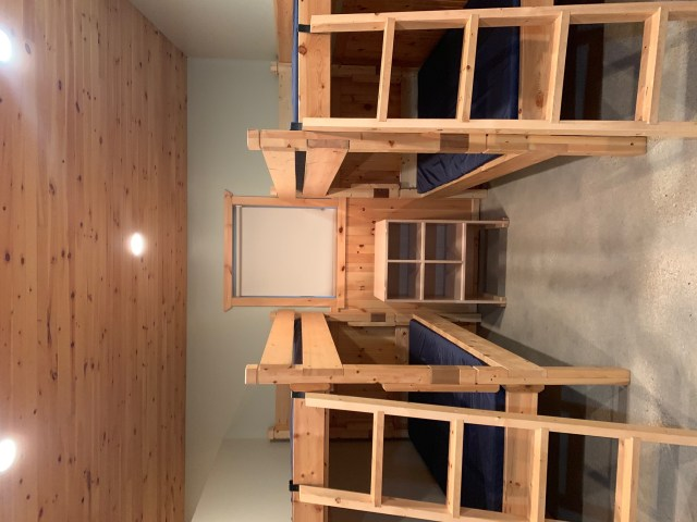 a room with 4 wooden bunkbeds, ladders to reach the top bunk, a wooden ceiling, and a shelf for shoes in the middle between the beds.