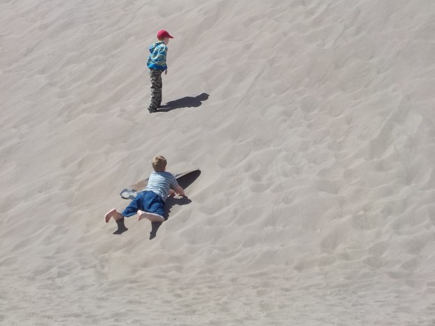 Kids playing on sand dunes.
