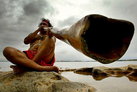 A photograph featuring an aboriginal didgeridoo player sitting on the beach with his instrument.