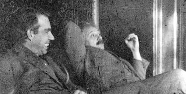 A historical black and white photograph showing Niels Bohr in conversation with Albert Einstein.