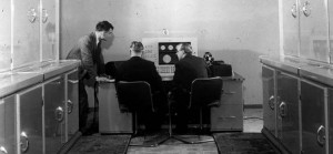 A black and white photograph showing Alan Turing and his work colleagues using the Mark I computer.