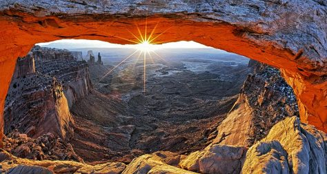 A beautiful photograph showing rock arches at National Park - Mesa Arch starburst panorama.