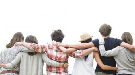 A photograph of a group of friends hugging each other. Friends or Fourth Cousins.