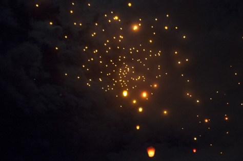 A photograph showing sky lanterns floating up in the night.