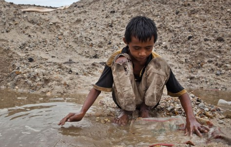 A photograph showing a young child labouring at an Indonesian tin mine.