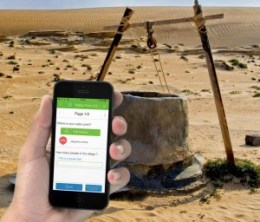 A photomontage showing a left hand holding a smartphone, which can be used to pinpoint the precise location of a remote well in the Saharan desert, seen here in the background.