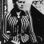 A black and white photograph of a young Marie Curie sporting a stripy tailored jacket.