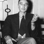 """A black and white photograph of physicist Robert Oppenheimer, pictured sitting down and smoking, with his post-war """"Bold Look"""" wide short tie."""
