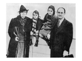 Enrico and Laura Fermi with their young family arriving in America - the boy and girl pictured sitting on a railing between their smiling parents.