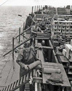 A black and white photograph showing naval personnel dumping chemical shells at sea.