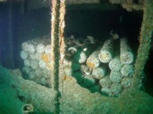 A photograph showing underwater stockpiled rusty ammunition shells.