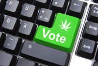 "A close-up photograph showing a computer keyboard: the large <Enter> key has been replaced by a green key with a little cannabis leaf symbol, spelling the message: ""Vote Cannabis""."