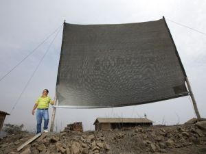 "A photograph showing Abel Cruz of ""Peruvians without Water"" standing next to one of the fog catcher nets installed in Villa Maria de Triunfo, near Lima. Photograph: AZCentral"