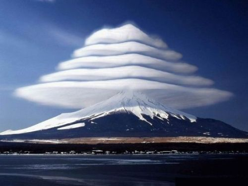"A photograph showing ""pile d'assiettes"" (or pile of plates) clouds over Mount Fuji in Japan. This is the usual term for a series of lenticular clouds stacked one above the other caused by wave motion in multiple humid layers of air. The technical classification is Stratocumulus lenticularis duplicatus or AltocumuIus lenticularis duplicatus (height of cloud is base dependent)."