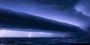 A photograph of a tube-shaped volutus cloud over the ocean, also showing lightning strikes from the ground to the cloud.