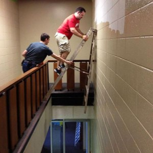 A man climbing precariously on a step-ladder while trying to decorate a stairwell.