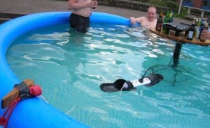 Several men bathing in an inflatable swimming pool in the middle of which is set up a table with various drinks and a sound system dangerously connected to mains power supply.