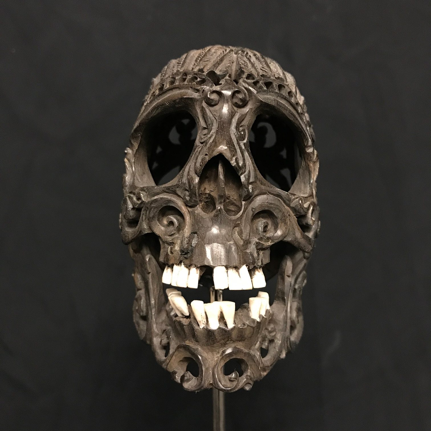 Intricately Carved Wooden Skull With Bone Teeth Mounted On A Metal Stand