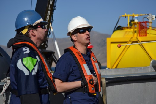 Cmdr. Ben Evans, commanding officer of NOAA Ship Rainier (right), and Peter Holmberg, physical scientist in Coast Survey's Hydrographic Surveys Division (left), observe a launch deployment on Rainier.