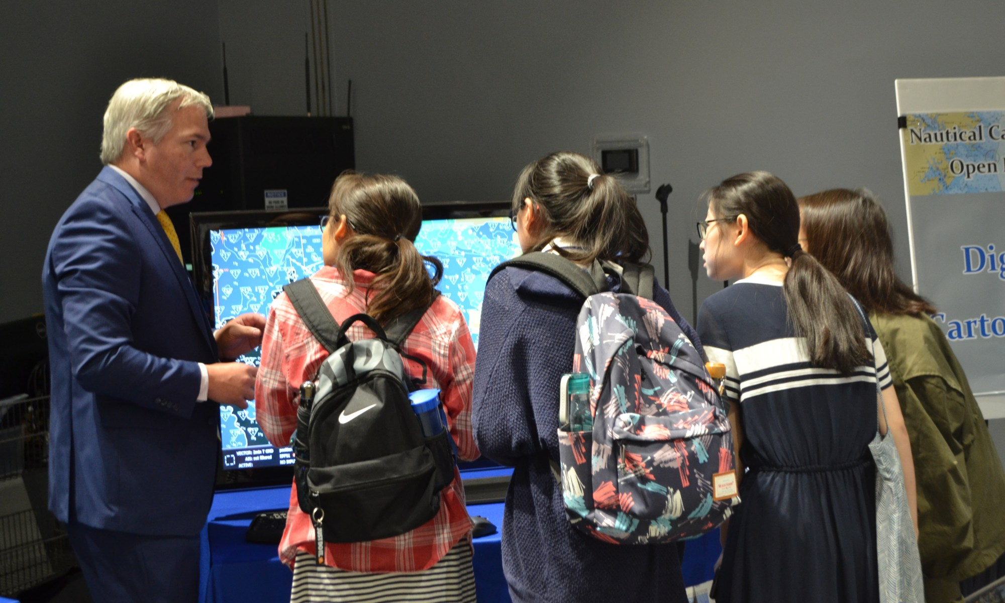 Sean Legeer shows a digital cartography display to visiting students.