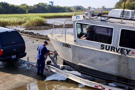 Lt. j.g. Colin Walker and Joshua Bergeron prepare to launch the team's response vessel into the Brunswick River.
