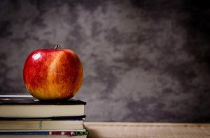 education illustration: apple on top of books with blackboard in background.