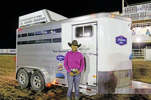 Standing by the trailer in rodeo grounds