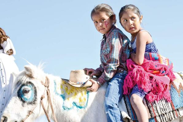 Navajo Times | Krista Allen A boy and a girl ride a miniature horse embellished with colorful paint during the 49th annual Western Navajo Fair parade on Saturday morning. The youngsters rode the horse along the parade route.