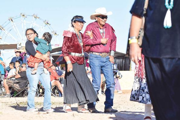 Navajo Times | Krista Allen Smiling radiantly, a couple participates in a round of skip dance at the 49th annual Western Navajo Fair song and dance on Saturday evening.