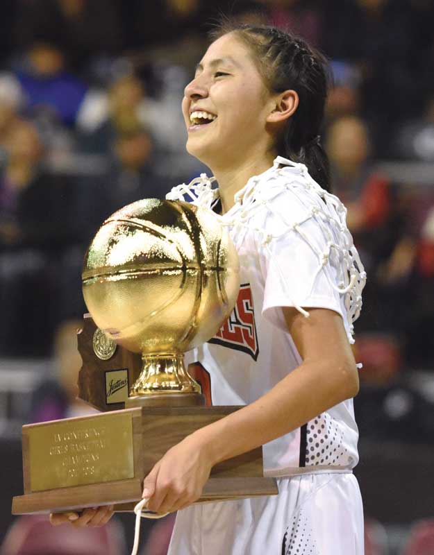 Navajo Times | Donovan Quintero St. Michael Lady Cardinal Ali Upshaw carries the team's Arizona 1A championship trophy Saturday , Feb. 24, 2018, in Prescott Valley, Ariz. The Lady Cardinals defeated the Baboquivari Lady Warriors, 60-44, to win the title.