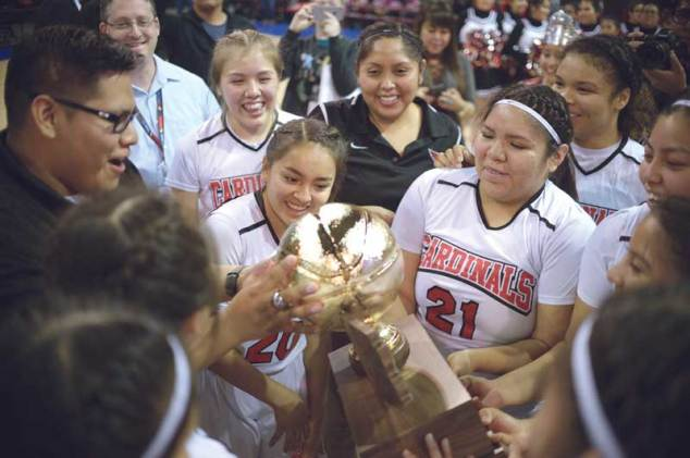Navajo Times | Donovan Quintero The St. Michael Lady Cardinals gather around the Arizona 1A girls championship trophy on Saturday after defeating the Baboquivari Lady Warriors, 60-44, at the Prescott Valley Events Center in Prescott Valley, Ariz.