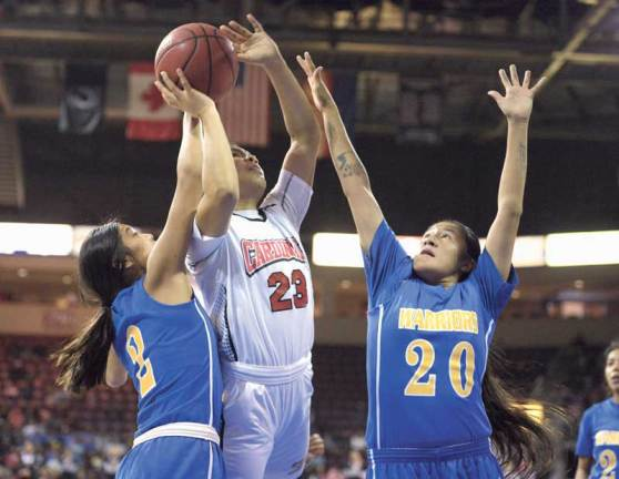 Navajo Times | Donovan Quintero St. Michael Lady Cardinal Delilah Nakaidinae (23) powers to the basket as Baboquivari Lady Warriors Blossom Gonzales (20) and Evelyn Young (2) defend Saturday during the Arizona 1A girls championship game in Prescott Valley, Ariz.