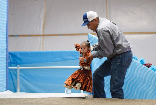 Navajo Times | Ravonelle Yazzie Hal Charley lifts his daughter, Alope Charley, up on stage during the baby contest at Ramah Navajo Fair and Rodeo on Aug. 24.