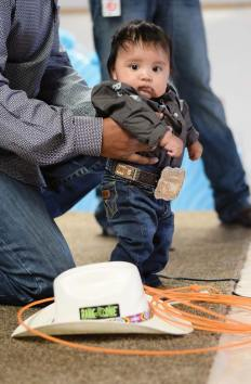 Navajo Times | Ravonelle Yazzie Stenson Thompson goes on stage in his cowboy gear during the baby contest held at Ramah Navajo Fair and Rodeo on Aug. 24.